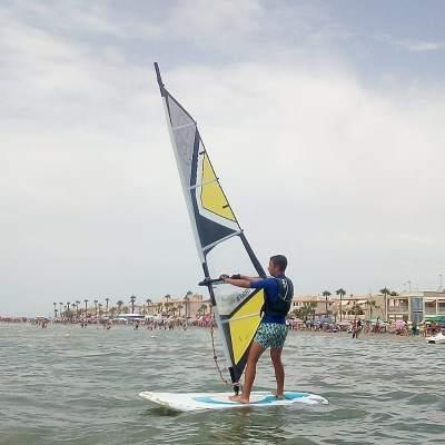 Hombre navegando en una tabla de windsurf en la playa