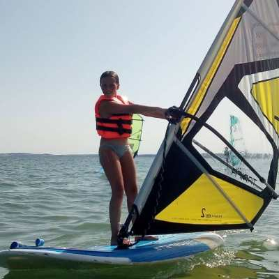 Niña practicando windsurf en el mar