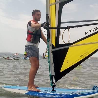 Hombre sobre la tabla de windsurf realizando la trasluchada