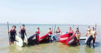 Grupo de niños y adolescentes con sus tablas de paddle surf a orillas del mar