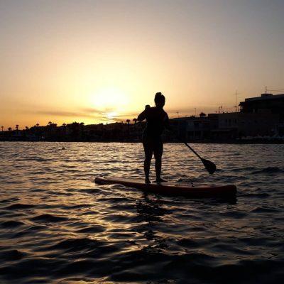 Mujer haciendo paddle surf al atardecer en Santa Pola