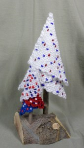 "The larger tree (""Fourth of July"" from the tree series) was woven using CSS. The smaller tree was woven with sport weight yarns which are not substantial enough to form a tight weave--particularly apparent in the white tier of the little tree. Also, the smaller tree was woven with the same colors but different beads. Those beads are larger than the white tree beads and I don't think they look as good."