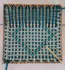 Toothpick points to bead correctly woven, but out of alignment.