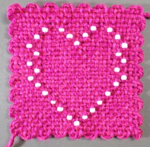 The finished heart off the loom--front. I admit I'm not crazy about those edges. You can get away with them when there are no beads present, but the beads really make them stand out.
