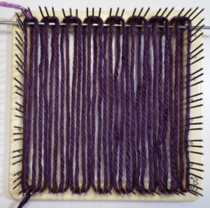 First row with needle in place. Note weaving starts at the top, or 3-4 edge of the loom.