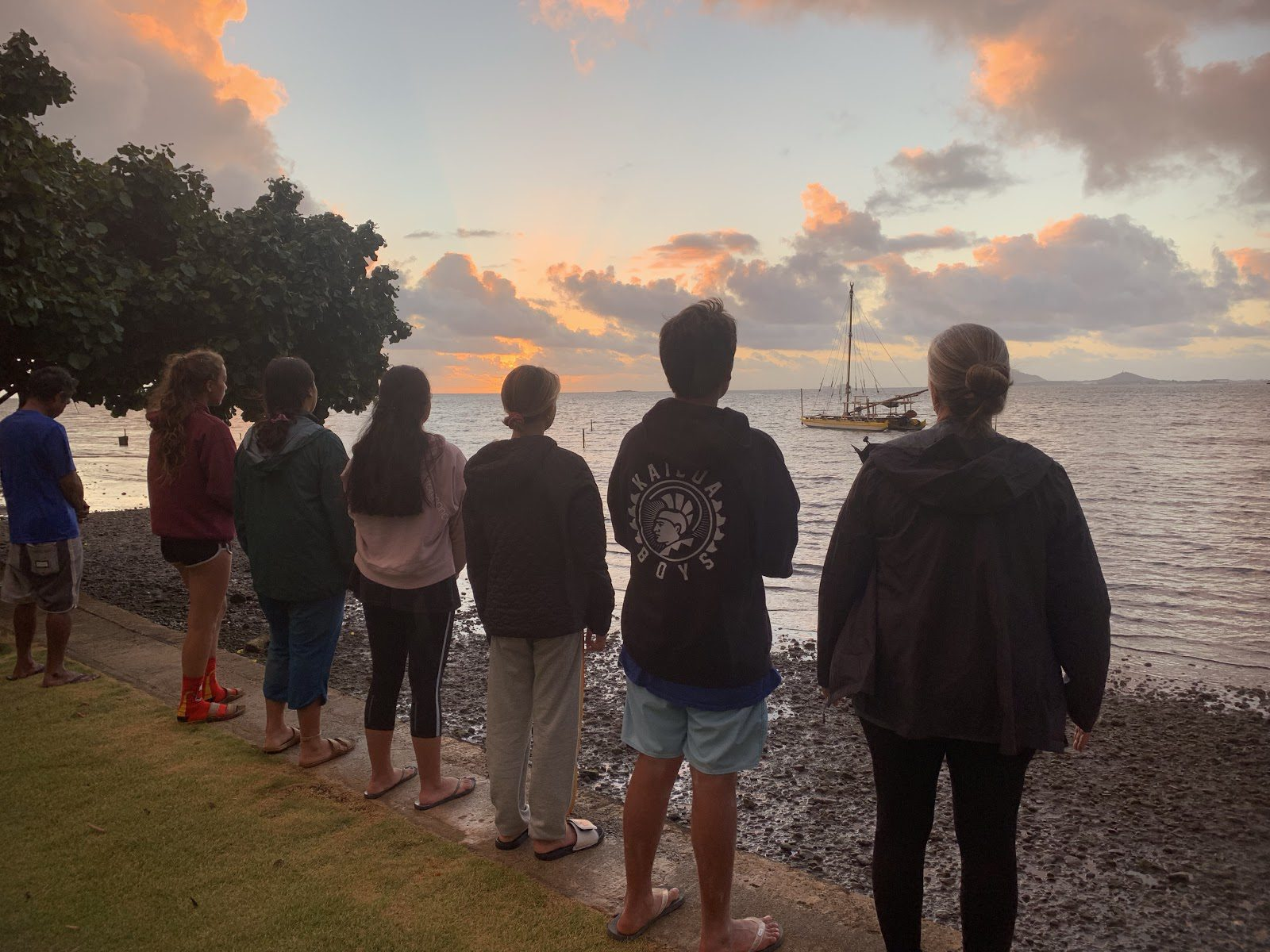 students standing at the shore looking out onto the horizon