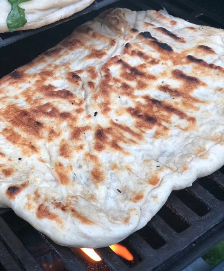 Grilled pizza dough that's golden and crispy with slight black char marks.