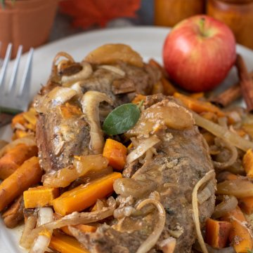 A oval white serving plater topped with pork tenderloin with onions, carrots, sweet potatoes and apples. There's a large silver serving utensil next to the pork with a red apple on the platter. There's a small rosemary plant in the background and red maple leaf