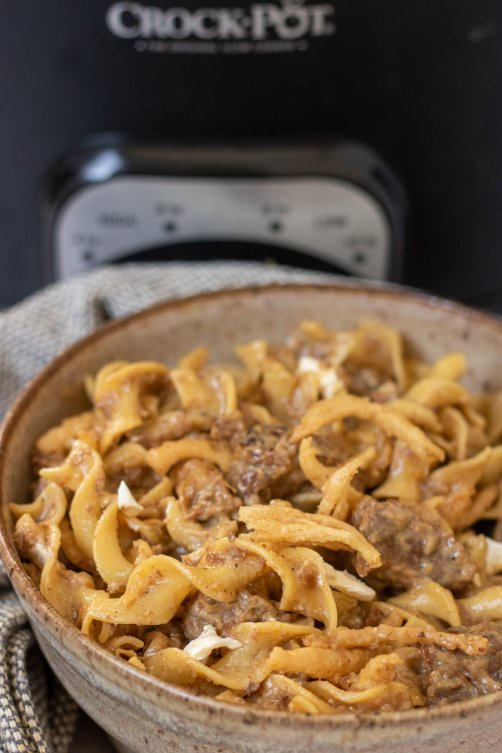 A brown specked bowl with egg noodles and beef stew meat. It's creamy and there's a black crockpot in the background.