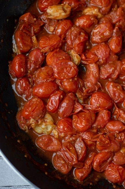 A large sauté pan of roasted cherry tomatoes with roasted garlic. The tomatoes are softened and cooked to a jam consistency