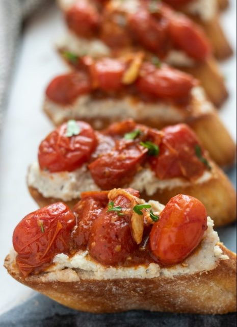 A marble serving board with slices of bruschetta that's topped with roasted tomatoes & garlic on top of a ricotta & bean purée. They're sprinkled with fresh parsley
