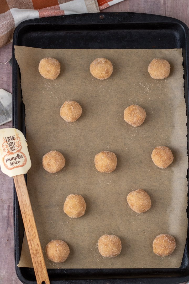 A cookie sheet lined with brown parchment paper topped with balls of snickerdoodle cookie dough.