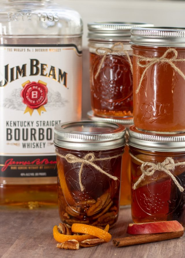 Small mason jars filled with infused whiskey that are stacked on top of each other. They have a hemp bow tied around them and there's a bottle of jim beam whiskey in the background