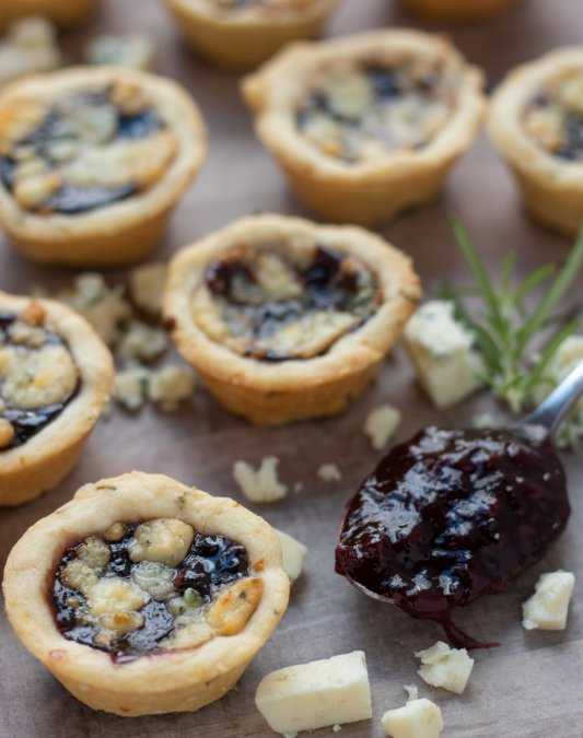 Several mini shortbread tarts that are filled with jam and topped with cheese. There's gorgonzola crumbles sprinkled around the tarts and a spoonful of blackberry jam in the background with a fresh rosemary sprig