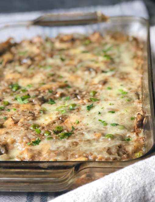 A rectangle casserole dish filled with cheesy cauliflower rice, mushrooms, peas and chicken. Made with a creamy balsamic sauce, Brie and Italian shredded cheese blend and baked until golden and bubbly.