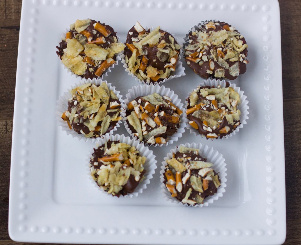 An overhead shot of mini sweet and salty brownie bites on a white square plate