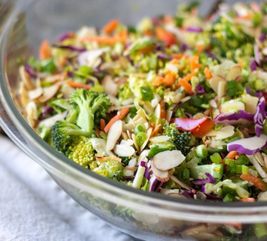 A big bowl of crunchy Asian salad with purple cabbage, shredded Brussels sprouts, carrots, lettuce and cucumber. It has slivered almonds and sesame seeds sprinkled on top.
