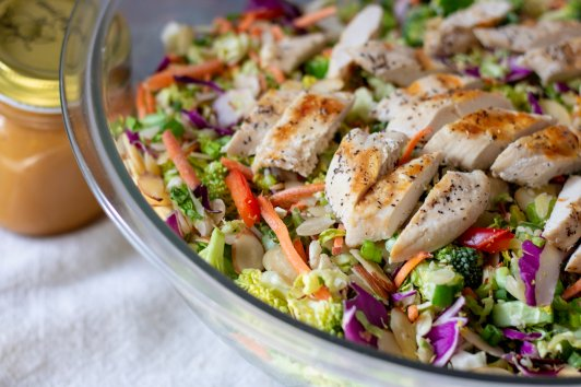 A big bowl of chopped Asian salad with grilled chicken, purple cabbage, broccoli, cucumber and lettuce. Topped with almonds and sesame seeds. A jar of easy Asian orange sesame peanut dressing is next to the salad bowl.