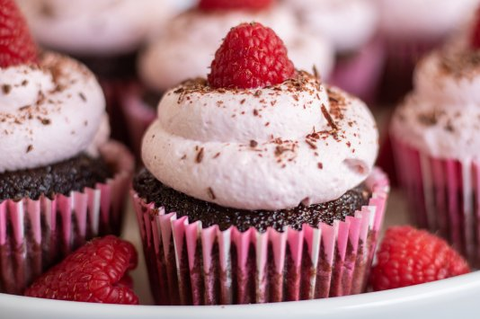 A closeup of a dark chocolate filled cupcake that's topped with raspberry whipped cream. Fresh raspberries and chocolate shavings are sprinkled on the plate