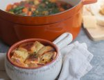 Ribolitta soup (Tuscan vegetable soup) is served in a crock and topped with crusty bread and cheese that's broiled until golden. There's a Dutch oven full of this hearty vegetable soup in the background with a cutting board of chunks of crusty bread.