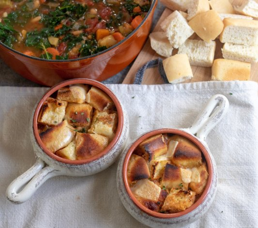 Two soup crocks filled with ribollita soup and topped with golden crusty bread and cheese. A pan of vegetable soup is in the background with a side of bread.