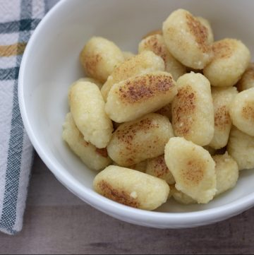 A white bowl of homemade cauliflower gnocchi that have been pan fried and golden. They're a copy cat version of Trader Joe's