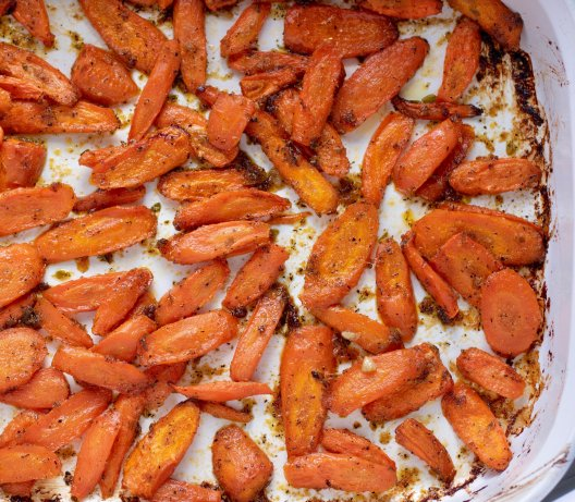 A white casserole dish of thin sliced roasted carrots with a maple lemon ginger glaze. They're oven roasted for an easy vegetable side dish