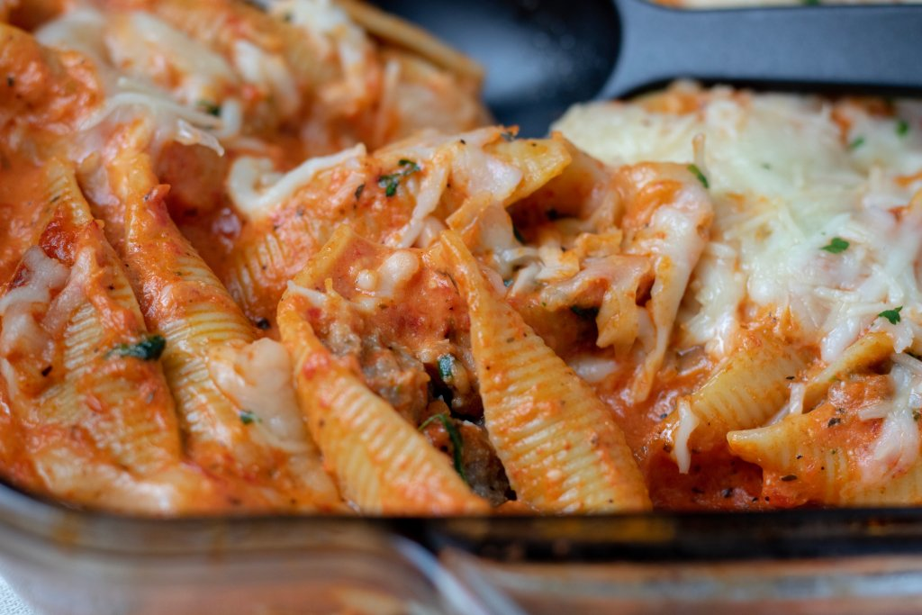 A glass baking dish filled with stuffed shells with a serving spoon scooping out a shell. They're filled with sausage, spinach and goat cheese and topped with a creamy red pepper sauce and mozzarella cheese