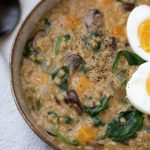 A brown speckled bowl filled with cheesy oatmeal made from steel oats. It's cooked with spinach and mushrooms and topped with a boiled egg.