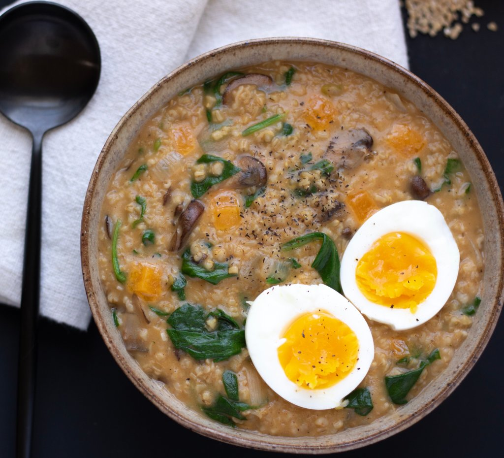 A bowl of savory oatmeal with spinach and mushrooms. A soft boil egg is cut in half and placed on top of the oatmeal. Raw steel oats are spilled in the background.