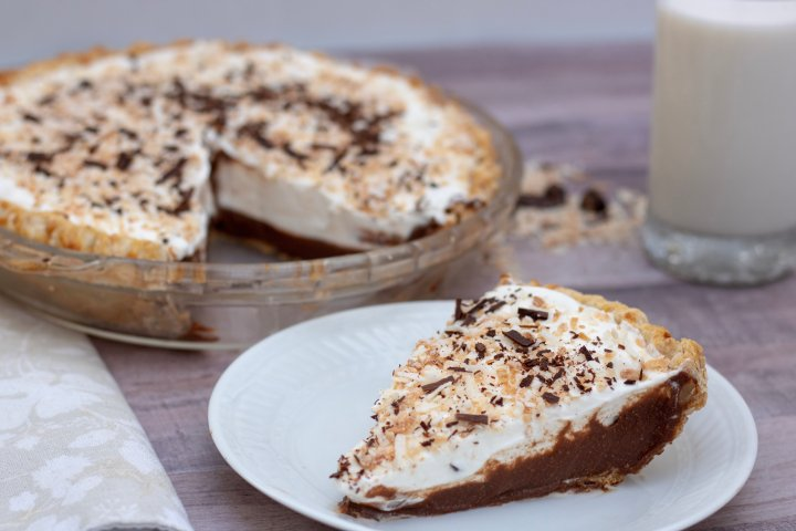 A slice of cream pie on a white plate. The rest of the chocolate coconut cream pie is in the background. A glass of milk is in the background.