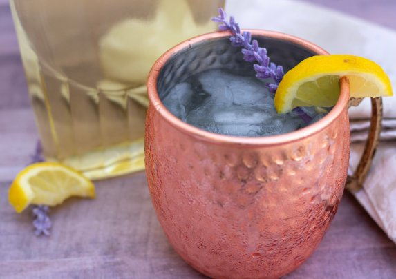 A copper Moscow mule mug that's dripping with condensation from being nice and cold. It's made with lavender and lemon vodka. A lavender bud and fresh lemon slice are garnished in the Moscow mule cocktail
