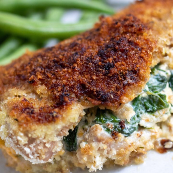 A boneless pork chop that's got a golden and crispy panko crust. It's stuffed with spinach and cheese that's spilling out of the middle. It's on a dish with green beans on the side.
