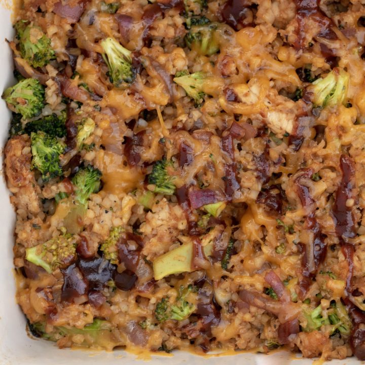 A cheesy low carb casserole made with cauliflower rice, broccoli, bbq chicken and cheese. The BBQ sauce is drizzled on top and the cheesy is melted and golden