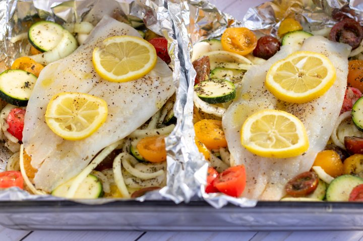 """A glass 13x9"""" baking dish with two foil packets that are filled with vegetables and topped with white fish. It's to be baked in the oven for an easy family dinner that's healthy and quick to make. It's got vibrant colorful cherry tomatoes, sliced zucchini and onions. You can see the fish is drizzled with olive oil and sprinkled with salt and pepper."""
