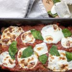 A loaf pan of Italian meatloaf that's topped with marinara and fresh mozzarella slices that are melted and slightly golden. It's finished with fresh basil slices.