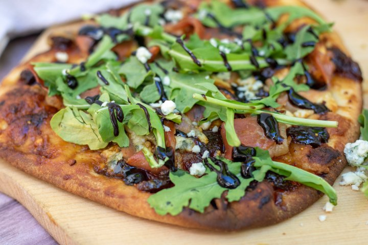 A side shot of flatbread pizza that's sitting on a pizza paddle. You can see the fresh arugula and blue cheese crumbles. It's got a golden crispy crust and is drizzle with balsamic