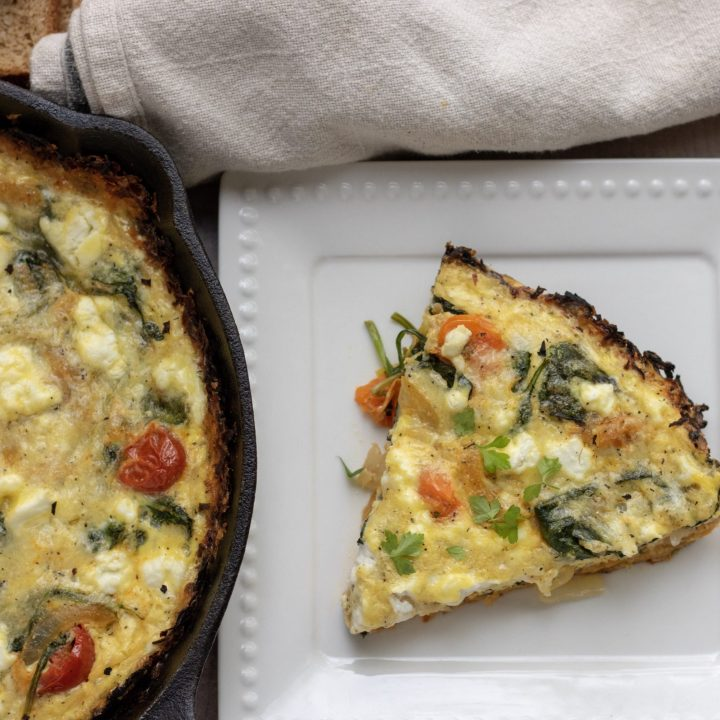 A part of a cast iron pan with quiche. There's a white dish next to it with a slice of quiche with roasted tomatoes, caramelized onions and spinach.