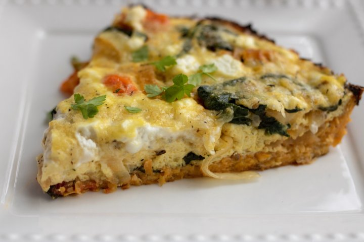 A slice of crustless quiche that's made with shredded sweet potato. It's garnished with fresh parsley. You can see the creamy goat cheese, bursted cherry tomatoes, fresh spinach and caramelized onions.