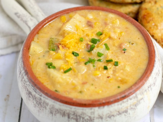 a white crock filled with creamy summer corn chowder. It's topped with cheddar cheese and chives and loaded with zucchini and potatoes. There's a couple of cheddar herb biscuits in the background.