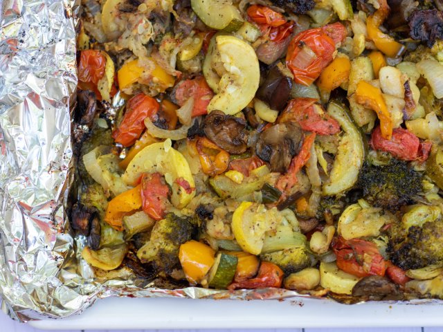 a medley of summer vegetables that have been roasted on the grill until tender and crispy. Some of them have a light char on the outside from the grill. There's squash, eggplant, tomatoes, onion and broccoli.