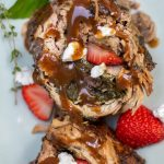 Pork tenderloin that's stuffed with sautéed spinach, sliced strawberries, and goat cheese has been sliced and drizzled with balsamic gravy. It's served on a light green serving platter and there's fresh strawberry slices and goat cheese on the platter