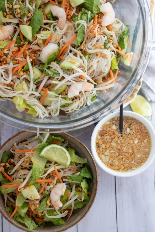 A large glass bowl of spring roll salad. There's a smaller bowl in the front with rice noodles, carrots, bean sprouts, cucumber, fresh mint and basil. It's topped with shrimp and crushed peanuts. Next to the bowls is a smaller bowl with peanut dressing with a small spoon in it.