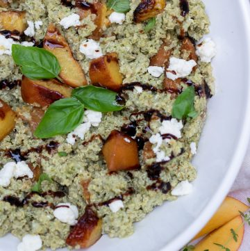 A white serving bowl with pesto quinoa, grilled peaches, goat cheese crumbles and balsamic drizzle. It's garnished with fresh basil leaves. There's a couple of fresh peach slices and fresh thyme sprigs next to the bowl in the background.