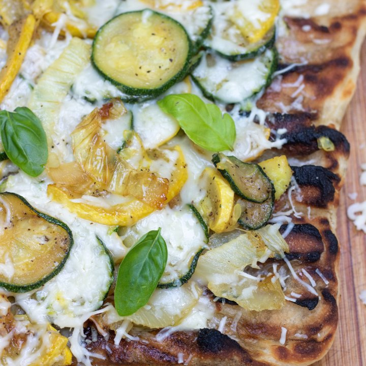 Grilled pizza on a wooden cutting board with shredded cheese sprinkled on the board. The crust has slight char marks on it and it's topped with summer squash, onions and fresh basil