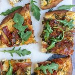 Cut up pieces of flatbread naan pizza that's topped with crispy salami pieces, fresh arugula and cheeses. The salami is browned and crispy on top.