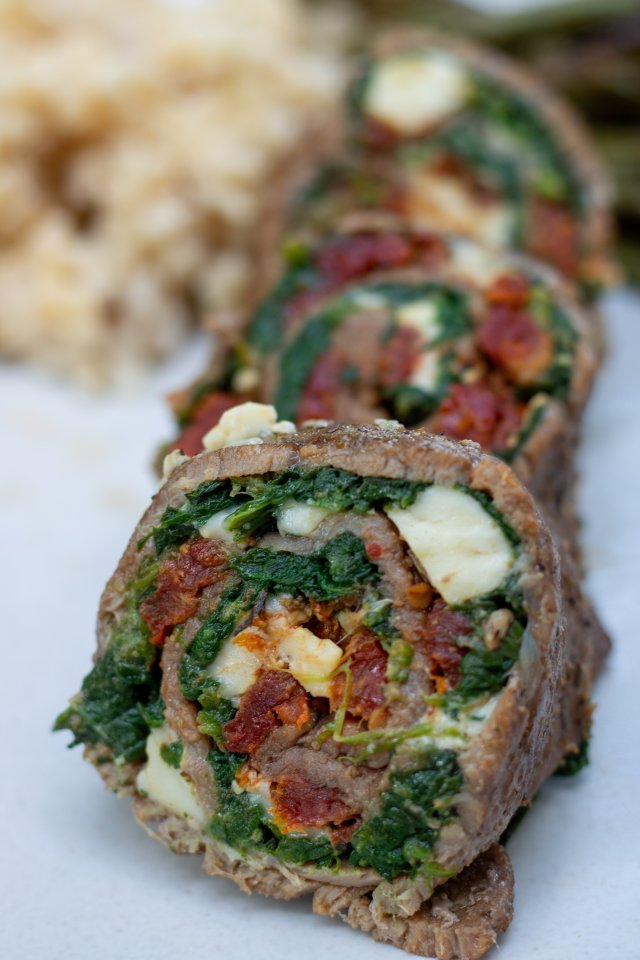 sliced steak roll ups that look like pinwheels. You can see they've been stuffed with cheese, spinach and sun dried tomatoes. There's 3 round slices on a serving plate.