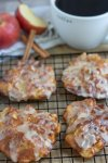 A cooling rack with brown parchment underneath it with air fried apple fritters on top. They're golden brown and have glaze dripping down the sides. There's a cup of coffee in the background with a red apple and two whole cinnamon sticks.