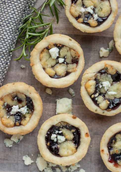 Mini tarts topped with gorgonzola cheese and filled with blackberry jam. There's gorgonzola crumbles sprinkled on a wood background with a fresh rosemary sprig.