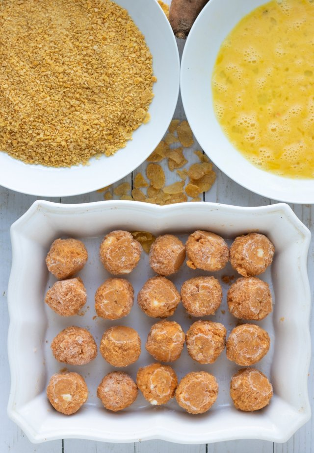 A rectangle white baking dish filled with sweet potato & goat cheese balls. There's a white bowl with corn flake crumbs and a bowl with beaten eggs.